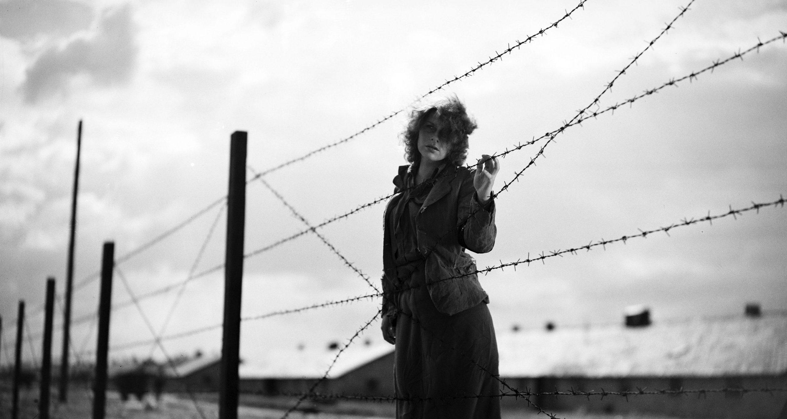 kadr z filmu Ostatni etap, kobieta w obozie koncentracyjnym dotyka drutu kolczastego