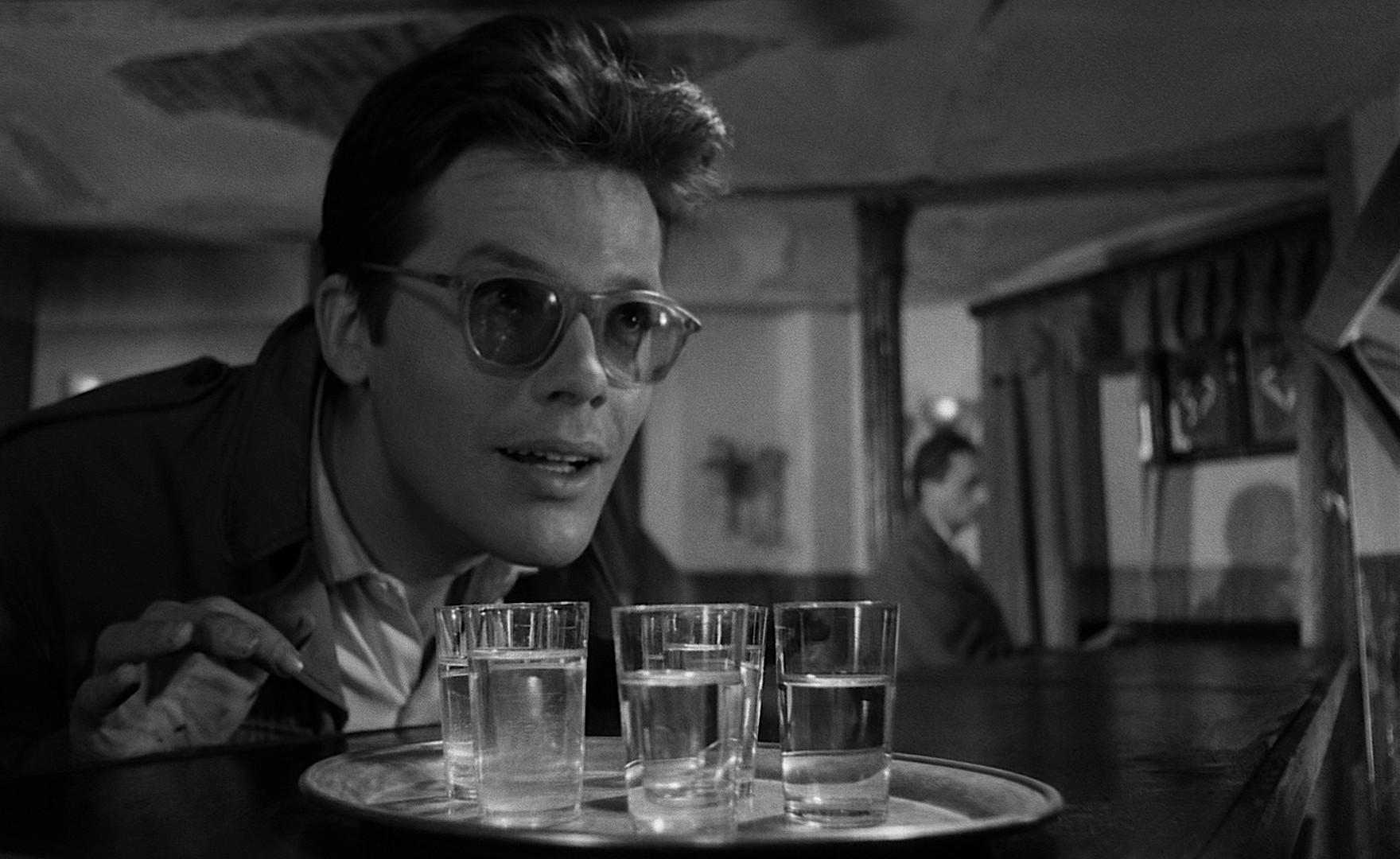 kadr z filmu Popiół i diament, Zbigniew Cybulski nachyla się nad tacką ze szklankami wódki