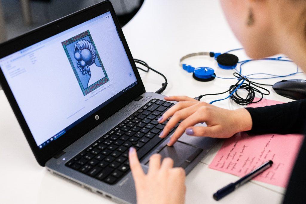 zdjęcie przedstawia laptop z otwartą stroną filmoteki szkolnej, przy komputerze siedzi użytkowniczka