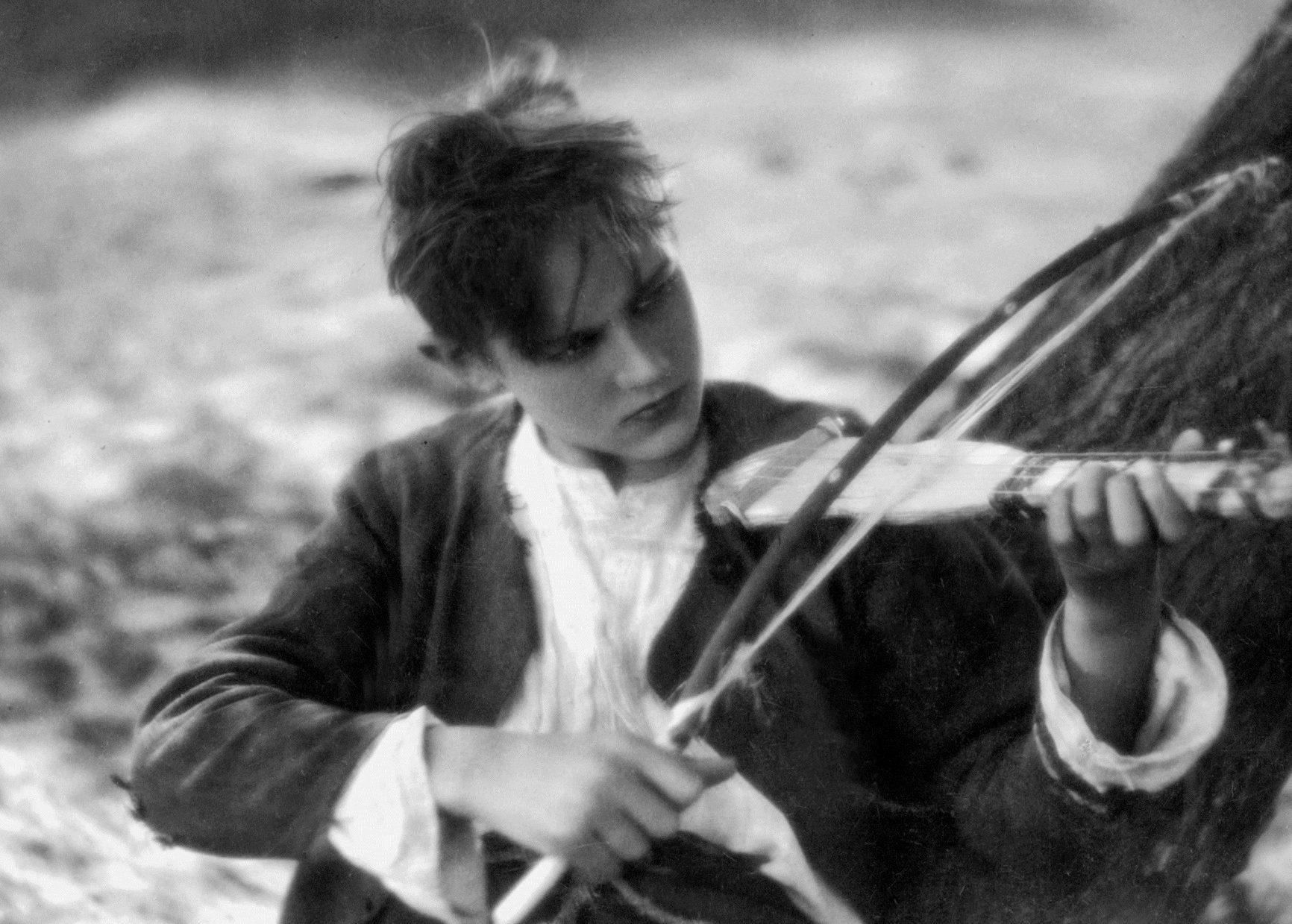młody mężczyzna gra na skrzypcach