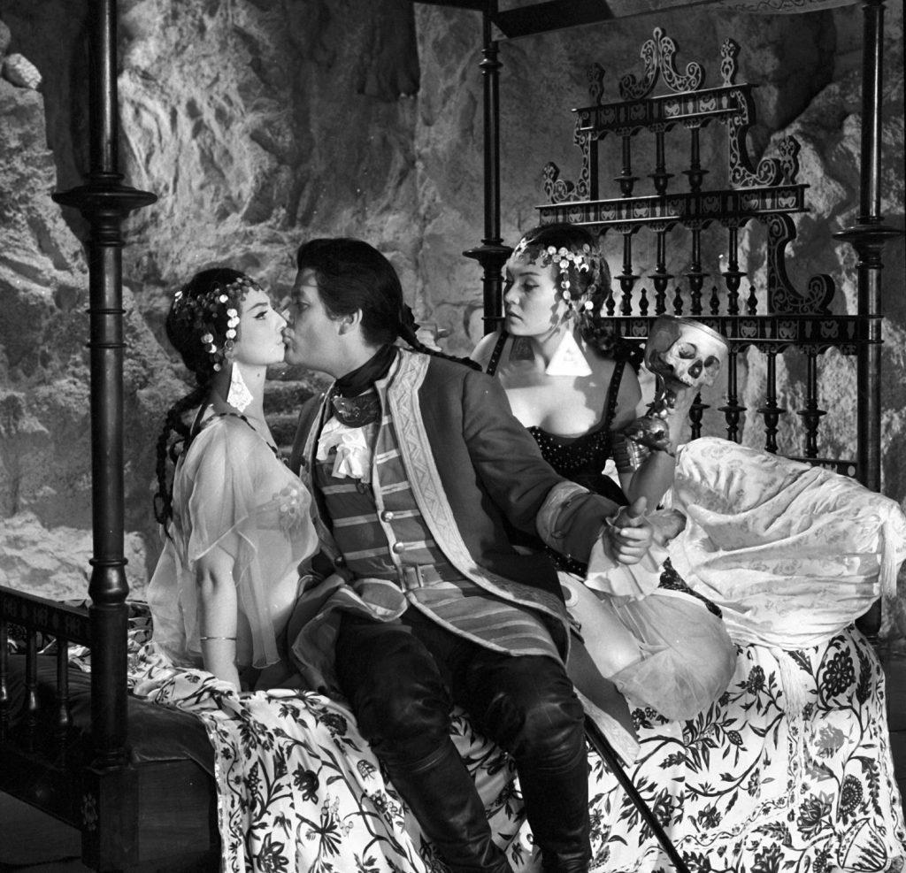 wnętrze z XVIII wieku, wytworna komnata, mężcyzna w szlacheckim stroju całuje kobietę, obok siedzi druga młoda kobieta