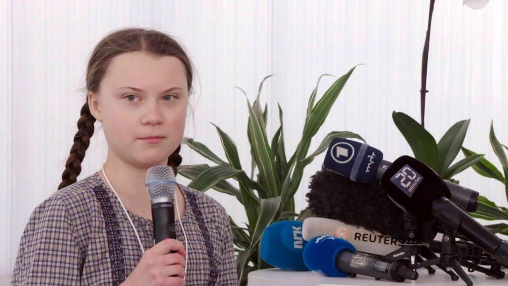 Nastoletnia aktywistka klimatyczna Greta Thunberg z mikrofonen
