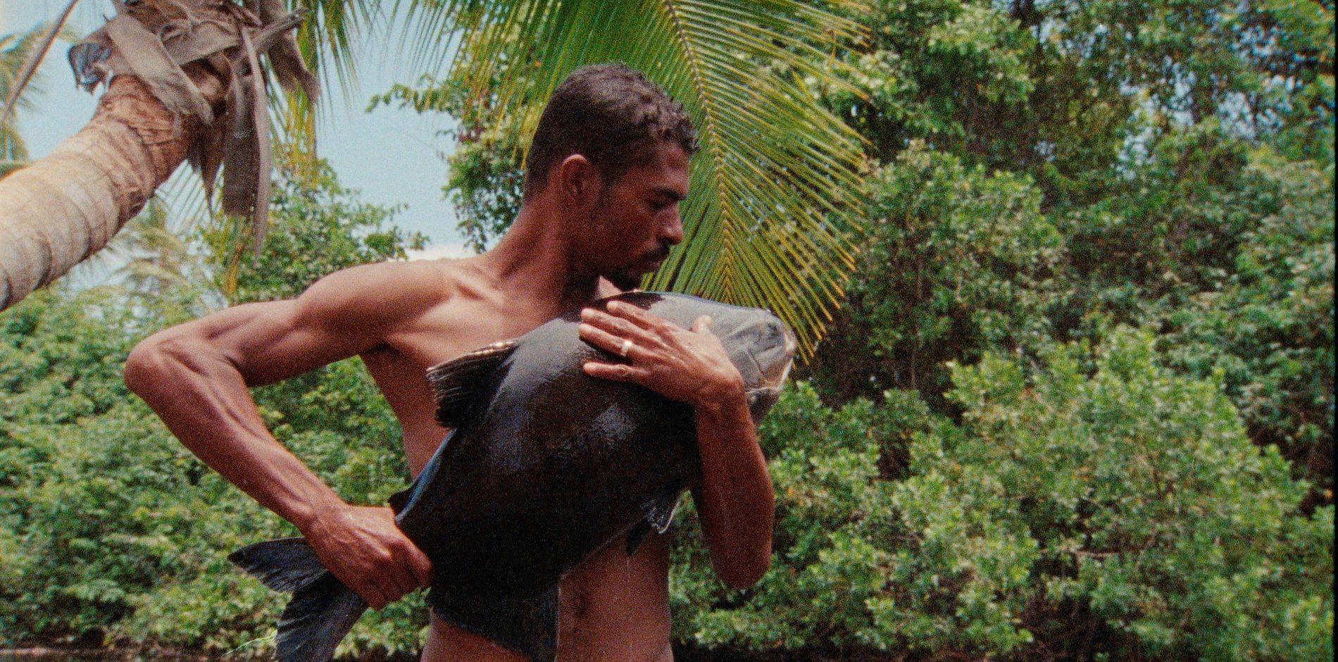 na zdjęciu mężczyzna stojcy po kolana w tropikalnej rzece trzyma w ręku rybę