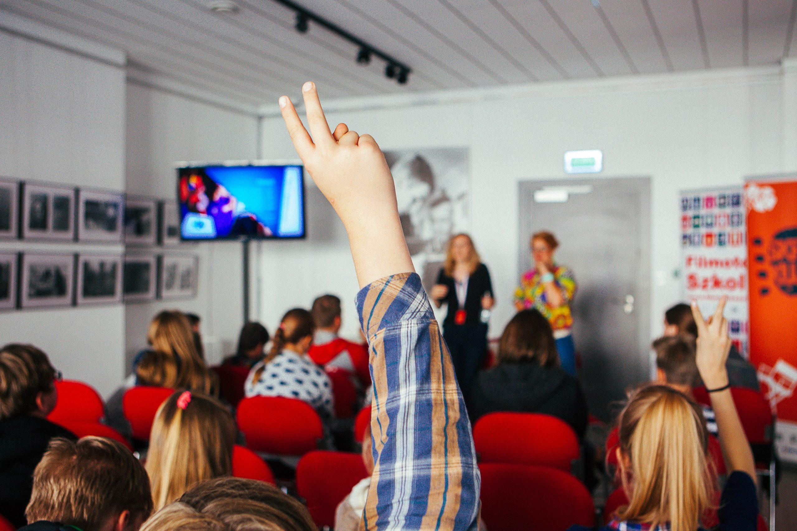 sala szkolna multimedialna, uczniowie siedzą na pufach, jedna osoba podnosi rękę