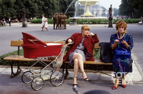 dwie młode kobiety siedzą na ławce pzry fontanie, jedna ma wózek dziecięcy