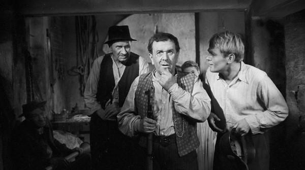 trzech mężczyzn w średnim wieku około 50 lat w wiejskiej izbie, jeden z nich wykonuje gest jakby się zastanawiał